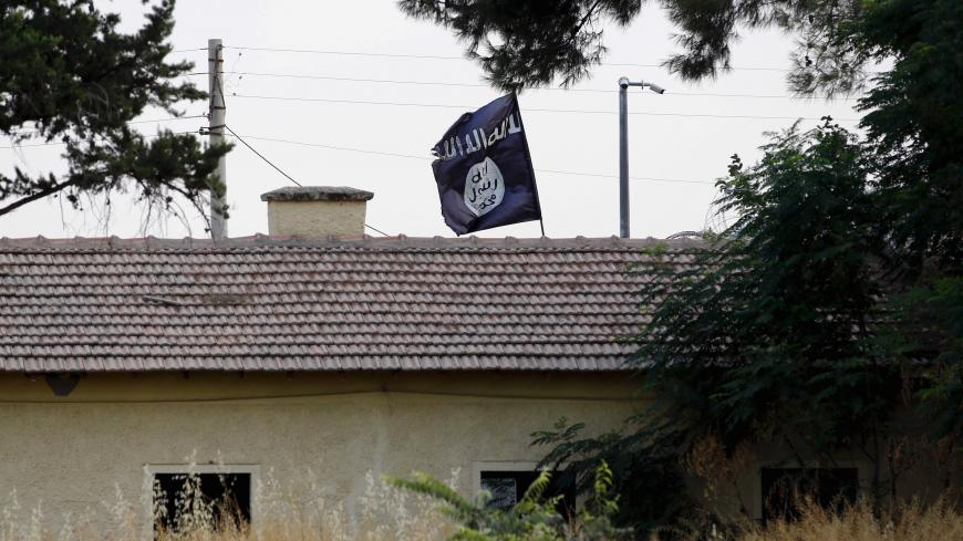 An Islamic State flag flies over the custom office of Syria's Jarablus border gate as it is pictured from the Turkish town of Karkamis, in Gaziantep province, Turkey August 1, 2015. Karkamis is a Turkish town of 10,500 people that sits directly opposite the border post. Shut for more than a year, the military sealed the crossing with a breeze block wall a few months ago. Behind it, just inside Syria, the black flag of Islamic State flaps in the breeze. Karkamis lies on the northeastern edge of a rectangle o