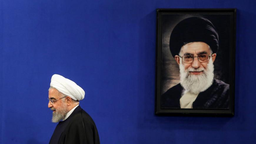 Iranian President Hassan Rouhani walks past a portrait of Supreme Leader Ayatollah Ali Khamenei as he arrives for a news conference in the capital Tehran, on February 16, 2020. - Iran's President Hassan Rouhani ruled out resigning and vowed to see out his term, even as he admitted he had offered to step aside twice since being elected. Speaking ahead of a general election next Friday, Rouhani also appealed to voters to turn out despite the fact that many moderate and reformist candidates were disqualified f
