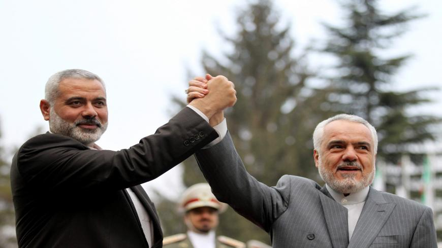 Iran's First Vice President Mohammad Reza Rahimi (R) and Ismail Haniya, Palestinian Hamas premier of Gaza, raise their hands upon the latter's arrival for a meeting in Tehran on February 10, 2012. AFP PHOTO/ATTA KENARE (Photo credit should read ATTA KENARE/AFP via Getty Images)