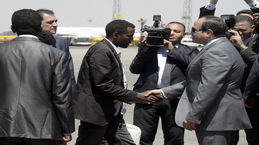 "Egyptian President Abdel Fattah al-Sisi (R) receives an Ethiopian man who Sisi said was ""rescued"" from war-torn Libya alongside 26 of his compatriots by Egypts security services upon their arrival at Cairo airport on May 7, 2015. It was not immediately clear how the Ethiopians were rescued, but Sisi's office said the group flown in on an Egyptian plane was ""liberated by Egyptian and Libyan security services"". AFP PHOTO / STR        (Photo credit should read STR/AFP via Getty Images)"