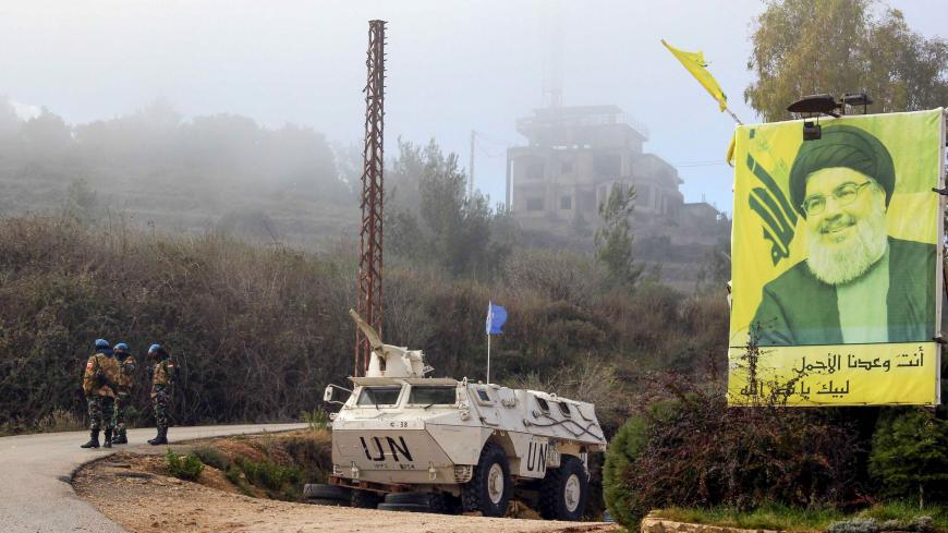 "A United Nations Interim Forces in Lebanon (UNIFIL) armoured vehicle is parked under a portrait of Hezbollah leader Hassan Nasrallah on a side road in the southern Lebanese town of Kfar Kila near the border with Israel on January 3, 2020. - Following this morning's killing of Iranian commander, Major General Qasem Soleimani, Lebanon's Iran-backed Hezbollah movement called for the missile strike by Israel's closest ally, to be avenged. ""Meting out the appropriate punishment to these criminal assassins... wil"