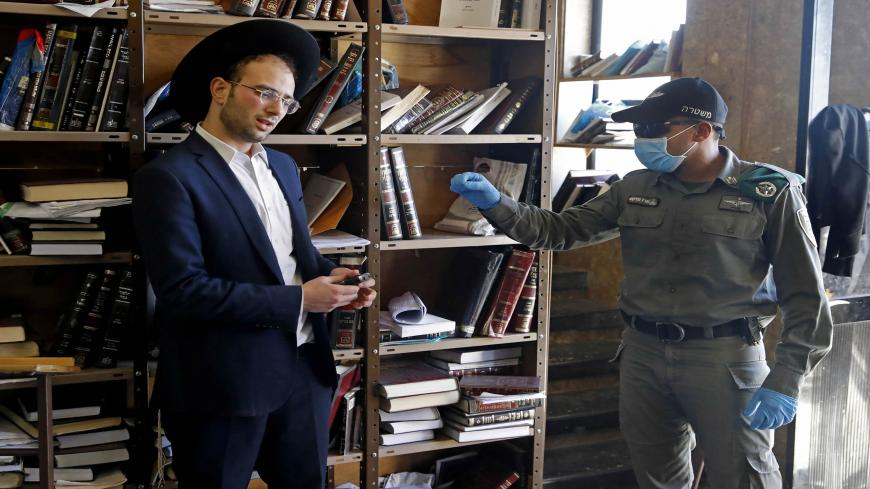 An Israeli police officer, dressed in protective outfit, speaks to a Yeshiva (Jewish educational institution for studies of traditional religious texts)student, in the Israeli city of Bnei Brak on April 2, 2020, during a control to insure that social distancing measures imposed by Israeli authorities meant to curb the spread of the novel coronavirus are being respected. (Photo by JACK GUEZ / AFP) (Photo by JACK GUEZ/AFP via Getty Images)