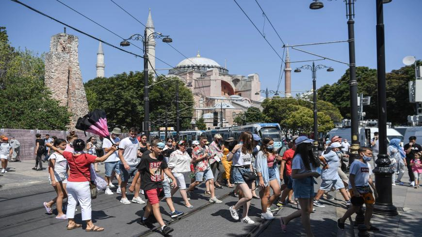 A group of tourists walk past Hagia Sophia as they go toward the historical Sultanahmet district on July 28, 2020 in Istanbul. - The Council of State, the highest administrative court, on July 10, 2020 unanimously cancelled a 1934 decision by modern Turkey's founder Mustafa Kemal Ataturk to turn it into a museum, saying it was registered as a mosque in its property deeds. (Photo by Ozan KOSE / AFP) (Photo by OZAN KOSE/AFP via Getty Images)