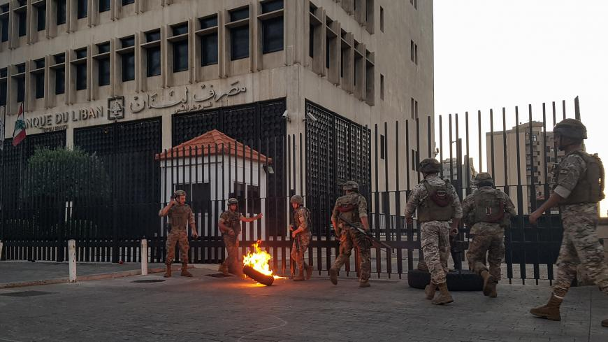 Lebanese Army soldiers roll away a flaming tire from the fence surrounding the local branch of the Banque du Liban (Lebanese Central Bank) as protesters gather to demonstrate against dire economic conditions in the northern city of Tripoli on June 11, 2020. - The Lebanese pound sank to a record low on the black market on June 11 despite the authorities' attempts to halt the plunge of the crisis-hit country's currency, money changers said. Lebanon is in the grips of its worst economic turmoil in decades, and