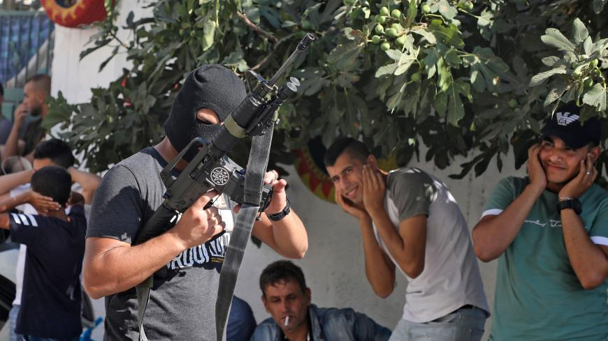 Palestinians cover their ears as a masked man fires a volley from his rifle, during the funeral of Dalia Ahmed Suleiman Samudi, 23, in Jenin city in the occupied West Bank on August 7, 2020, who was killed by Israeli fire during clashes. - Samudi died of a gunshot wound after being shot near the site of clashes between Palestinian youths and Israeli troops in the occupied West Bank, Palestinian officials said. (Photo by JAAFAR ASHTIYEH / AFP) (Photo by JAAFAR ASHTIYEH/AFP via Getty Images)