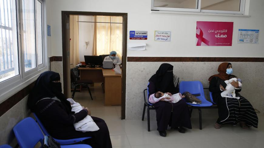 Palestinian women mask-clad due to the Covid-19 coronavirus pandemic wait with their children in a UN clinic  to take Polio vaccine and Rota virus vaccines at Bureij refugee camp in the central of Gaza Strip on September 9, 2020. (Photo by MOHAMMED ABED / AFP) (Photo by MOHAMMED ABED/AFP via Getty Images)