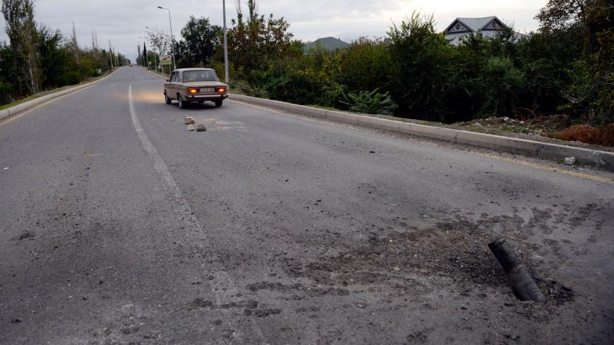A picture taken on September 28, 2020 shows an unexploded artillery shell on a road on the outskirts of the Azerbaijani city of Tartar during clashes between Armenian separatists and Azerbaijan over the breakaway Nagorny Karabakh region. (Photo by Tofik BABAYEV / AFP) (Photo by TOFIK BABAYEV/AFP via Getty Images)
