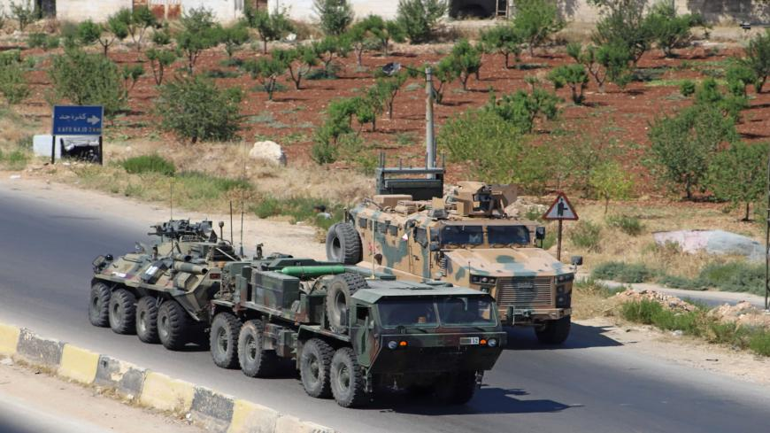A Turkish-Russian military convoy tows a damaged vehicle after its joint patrol was reportedly targeted on the strategic M4 highway, near the Syrian town of Urum al-Jawz in the south of the northwestern Idlib province, on August 25, 2020. - Russia and Turkey launched joint patrols along the M4 highway in March following a ceasefire agreement aimed at stopping heavy fighting in and around Idlib, the last major bastion of anti-government forces in Syria's civil war. (Photo by Abdulaziz KETAZ / AFP) (Photo by