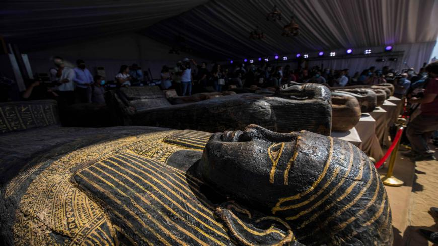 A picture taken on October 3, 2020 shows sarcophaguses, excavated by the Egyptian archaeological mission which discovered a deep burial well with more than 59 human coffins closed for more than 2,500 years, displayed during a press conference  at the Saqqara necropolis, 30 kms south of the Egyptian capital Cairo. - They were unearthed south of Cairo in the sprawling burial ground of Saqqara, the necropolis of the ancient Egyptian capital of Memphis, a UNESCO World Heritage site. Their exteriors are covered