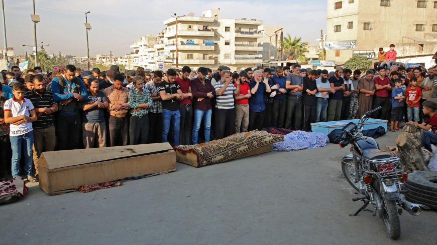 Syrians take part in the funeral of 10 fighters with the Turkey-backed Faylaq al-Sham rebel faction in Syria, in the northwestern city of Idlib, on October 26, 2020, following their death in a Russian air strike. - Air strikes by Syrian regime ally Russia killed 78 fighters from the turkey-backed Faylaq al-Sham faction when they targeted a training camp in the Jabal Duwayli area in Idlib province, the Syrian Observatory for Human Rights said. (Photo by Mohammed AL-RIFAI / AFP) (Photo by MOHAMMED AL-RIFAI/AF