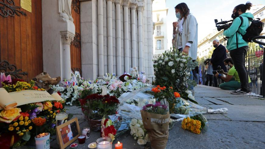 A woman pays homage in front of the Notre-Dame de l'Assomption Basilica in Nice on October 30, 2020 during a tribute to the victims killed by a knife attacker the day before. - A 47-year-old man believed to have been in contact with the suspected knifeman who killed three at a church in Nice has been detained for questioning, a judicial source said on October 30, 2020. The man was detained late Thursday after the attack at the city's Notre-Dame basilica by a 21-year-old Tunisian who arrived in France on Oct