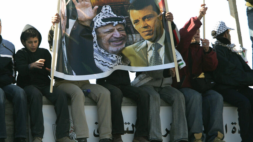 RAMALLAH, -:  Palestinians hold a banner showing late Palestinian leader Yasser Arafat (L) and Fatah MP Mohammed Dahlan during a rally in the West Bank city of Ramallah 11 January 2007, to mark the 42nd anniversary of the Fatah movement. Thousands of flag-waving chanting supporters of Palestinian president Mahmud Abbas's Fatah party poured into central Ramallah for a second rally in less than a week aimed at staging a show of force agains the ruling Hamas movement. AFP PHOTO/PEDRO UGARTE  (Photo credit shou