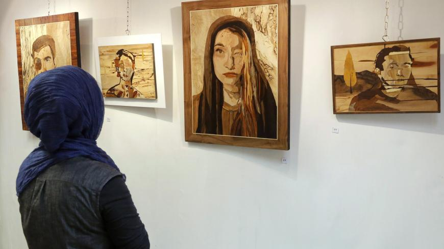 "A woman looks at art work made by Iranian victims of acid attacks at the Ashianeh gallery in Tehran on February 28, 2018. Acid attacks have been an occasional scourge in Iran, with a spate of incidents in 2014 triggering protests and claims they were linked to women wearing ""immodest"" clothing. Money raised by the show went to Iran's Association of Support of Acid Attack Victims.  / AFP PHOTO / ATTA KENARE        (Photo credit should read ATTA KENARE/AFP via Getty Images)"