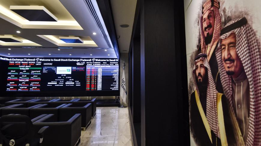 This picture taken December 12, 2019 shows (L) a view of the exchange board at the Stock Exchange Market (Tadawul) bourse in Riyadh displaying Aramco shares on the second day of their trading, along with a poster depicting Saudi Arabia's founder King Abdulaziz ibn Saud (C), his son and current King Salman bin Abdulaziz (R), and the latter's son Crown Prince Mohammed bin Salman (L) on display. - Energy giant Saudi Aramco's market value soared above $2 trillion as its share price surged again on its second da