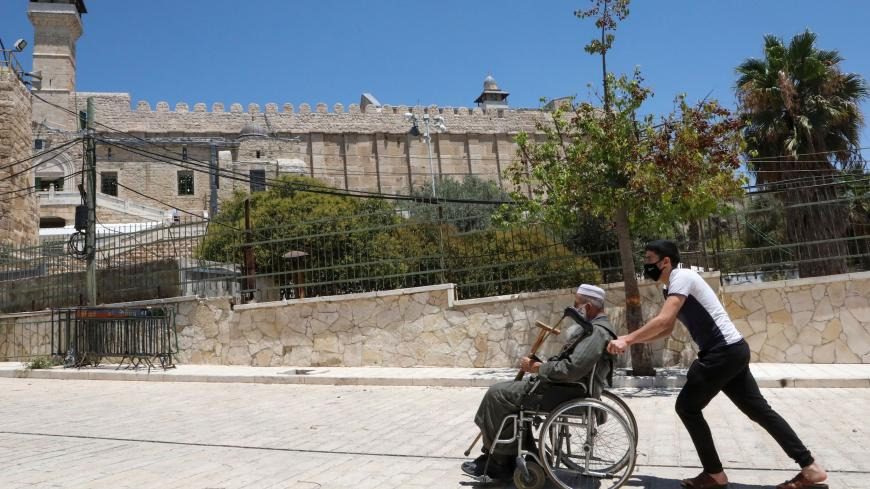 A Palestinian youth pushes an elderly man next to the Ibrahimi mosque (background), also known as the Tomb of the Patriarchs, in the occupied West Bank city of Hebron on August 7, 2020, amid the ongoing coronavirus pandemic crisis. (Photo by HAZEM BADER / AFP) (Photo by HAZEM BADER/AFP via Getty Images)