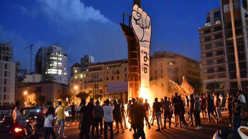 Lebanese youths gather around the Revolution fist, symbol of Lebanons October 2019 uprising, after it was set on fire during clashes between anti-government protesters and supporters of former prime minister Saad Hariri, in the capital Beirut's central Martyr's square, on October 21, 2020. - Hariri resigned as premier in October 2019 in the wake of unprecedented street protests, but he is now expected to make a comeback at the helm of the next government. Most parliamentary blocs have pledged support for Ha