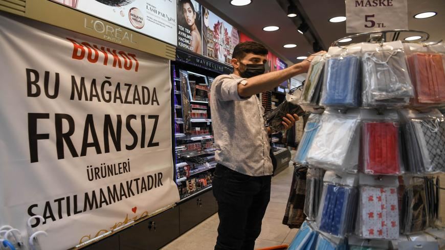 "An employee works in a shop near a banner reading ""Boycott, We do not sell French products in this shop"" on October 30,2020 in Istanbul. - Turkish President joined calls on October 26, 2020 for a boycott of French goods, ramping up a standoff between France and Muslim countries over Islam and freedom of speech. (Photo by Ozan KOSE / AFP) (Photo by OZAN KOSE/AFP via Getty Images)"
