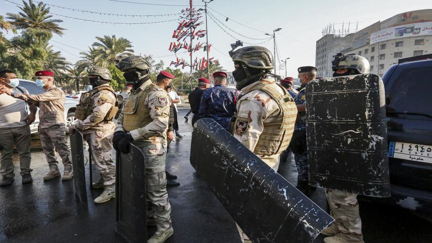 Members of the Iraqi security forces stand guard during the reopening of the Iraqi capital Baghdad's central Tahrir Square on October 31, 2020. - Iraqi authorities reopened Tahrir Square in central Baghdad, in a sign of easing tensions a year after the launch of an anti-government protest movement. Protests demanding a total overhaul of the ruling class lost momentum then ground to a halt in the spring due to the coronavirus crisis and rising US-Iran tensions. (Photo by Sabah ARAR / AFP) (Photo by SABAH ARA