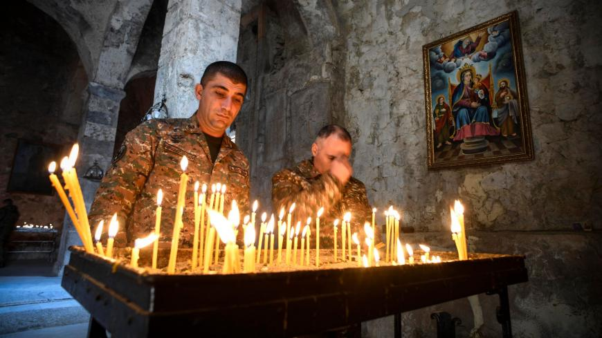 TOPSHOT - Armenian soldiers light candles as they pay a final tribute to fallen comrades at the 12th-13th century Orthodox Dadivank Monastery on the outskirts of Kalbajar on November 12, 2020, during the military conflict between Armenia and Azerbaijan over the breakaway region of Nagorno-Karabakh. - Kalbajar is one of the seven districts which will be transferred to Azerbaijan as part of a deal on Nagorno-Karabakh. (Photo by Alexander NEMENOV / AFP) (Photo by ALEXANDER NEMENOV/AFP via Getty Images)