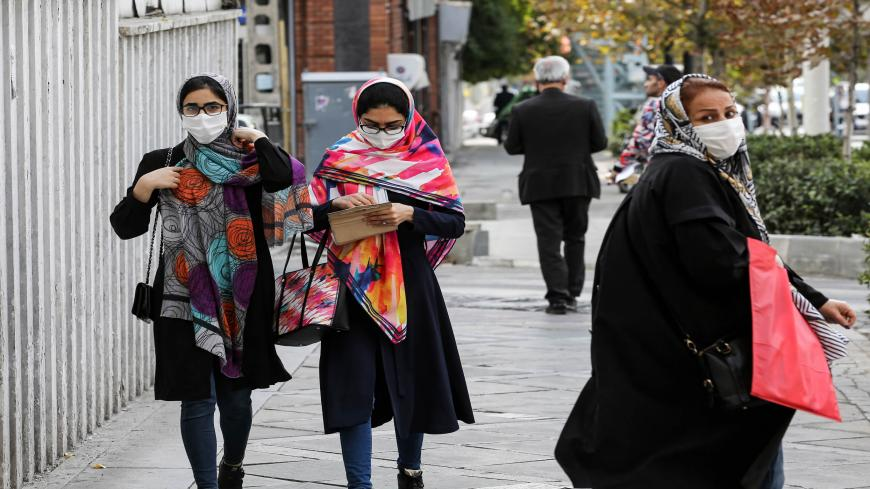 Women, mask-clad due to the COVID-19 coronavirus pandemic, walk along a street in Iran's capital Tehran on November 8, 2020. (Photo by ATTA KENARE / AFP) (Photo by ATTA KENARE/AFP via Getty Images)