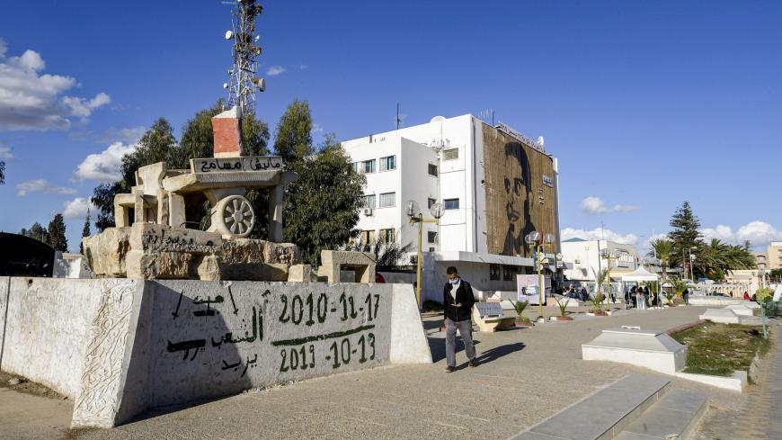"A man walks past a sculpture of Mohamed Bouazizi's cart (bearing text reading in Arabic: ""I do not forgive"") in the square named after him in the centre of the town of Sidi Bouzid in central Tunisia on October 27, 2020, the cradle of the 2011 Tunisian revolution where unemployment remains high ten years later. - The sister of Mohamed Bouazizi, whose self-immolation sparked a string of Arab uprisings, says she is ""very disappointed"" in Tunisia's revolution and has urged young Tunisians to continue the fight"
