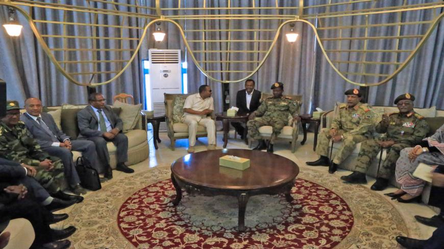 Ethiopia's Prime Minister Abiy Ahmed (C-L) meets with members of Sudan's ruling military council after his arrival at Khartoum international airport on June 7, 2019. - Ethiopia's prime minister arrived in Khartoum on June 7, seeking to broker talks between the ruling generals and protesters, as heavily armed paramilitaries remained deployed in some squares of the Sudanese capital after a deadly crackdown, leaving residents in 'terror'. (Photo by ASHRAF SHAZLY / AFP)        (Photo credit should read ASHRAF S