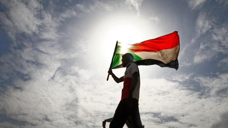 A Sudanese man waves his national flag as he takes part in a demonstration called for by the Sudanese Professionals Association (SPA) to denounce the July 29 Al-Obeid killings, in the capital Khartoum on August 1, 2019. - Thousands of Sudanese demonstrators rallied on August 1 against the killing of four students, as protest leaders and ruling generals were set to resume talks to thrash out remaining issues on transitioning to civilian rule. Tragedy struck Al-Obeid on July 29 when four high school students