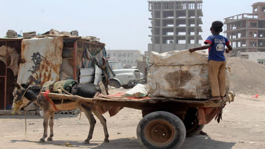 A Yemeni youth stands in the back of a transport donkey cart in the southern city of Aden, on September 16, 2020. - Yemenis are resorting to using donkeys to transport water and haul goods, as the long years of conflict that have ravaged the economy make gas-guzzling vehicles unaffordable for many. (Photo by Saleh Al-OBEIDI / AFP) (Photo by SALEH AL-OBEIDI/AFP via Getty Images)