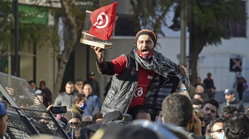 A Tunisian protester lifts a flag-clad birdcage during an anti-government demonstration on the Habib Bourguiba avenue in the capital Tunis, on January 19, 2021. - Tunisia braced for further protests after hundreds were arrested in four nights of street clashes between riot police and disaffected youths in cities across the North African country. (Photo by FETHI BELAID / AFP) (Photo by FETHI BELAID/AFP via Getty Images)