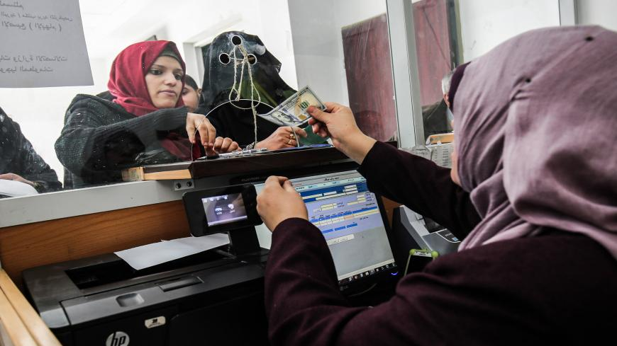 A Palestinian government employee receives a portion her his overdue salary at a post office in Rafah in the southern Gaza Strip on December 8, 2018, after the Hamas-run finance ministry had announced that the money would be distributed over the two days, with employees receiving 50 percent of their salaries. - Employees of the Hamas administration in the Gaza Strip began collecting their salaries for a second month on December 7, after Qatar pumped more money into the territory with Israel's blessings. The