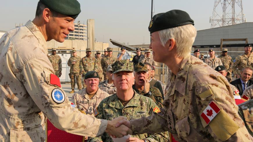Jennie Carignan (R), the incoming commander of NATO's Iraq mission, is greeted by Dany Fortin, the outgoing commander of NATO's Iraq mission, during the handover ceremony in the Iraqi capital Baghdad on November 26, 2019. (Photo by SABAH ARAR / AFP) (Photo by SABAH ARAR/AFP via Getty Images)