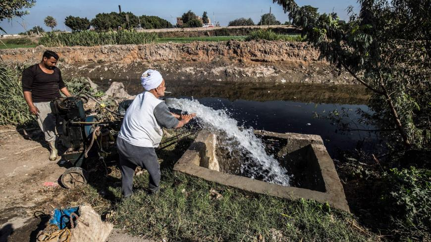 Egyptian farmer Mohamed Omar (C), 65, supplies his farmland with water from a canal, fed by the Nile river, in the village of Baharmis on the outskirts of Egypt's Giza province, northwest of the capital Cairo, on December 1, 2019. - Egypt has for years been suffering from a severe water crisis that is largely blamed on population growth. Mounting anxiety has gripped the already-strained farmers as the completion of Ethiopia's gigantic dam on the Blue Nile, a key tributary of the Nile, draws nearer. Egypt vi