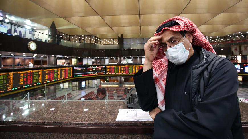 A Kuwaiti trader wearing a protective mask follows the market at the Boursa Kuwait stock exchange in Kuwait City on March 1, 2020. - Boursa Kuwait decided to close the main trading hall due to the COVID-19 coronavirus disease developments. Stock markets in the oil-rich Gulf states plunged on March 1 over fears of the impact of the coronavirus, which also battered global bourses last week. All of the seven exchanges in the Gulf Cooperation Council (GCC), which were closed the previous two days for the Muslim