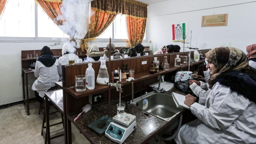 "This picture taken on November 26, 2020 shows Syrian students from the ""Aleppo University in Liberated Areas"", controlled by the pro-Turkey opposition, attending a tutorial at a laboratory facility in Marea in the rebel-controlled northern countryside of Syria's Aleppo province, while mask-clad due to the COVID-19 coronavirus pandemic. - The university had its first batch of 32 doctors to ever graduate after its founding in 2014, headquartered in Azaz for the past three years. Humanitarian workers fear any"