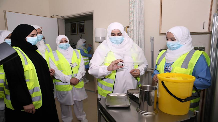 A healthcare worker prepares to administer the Pfizer-BioNTech COVID-19 vaccine in the Omani capital Muscat on December 27, 2020. (Photo by MOHAMMED MAHJOUB / AFP) (Photo by MOHAMMED MAHJOUB/AFP via Getty Images)