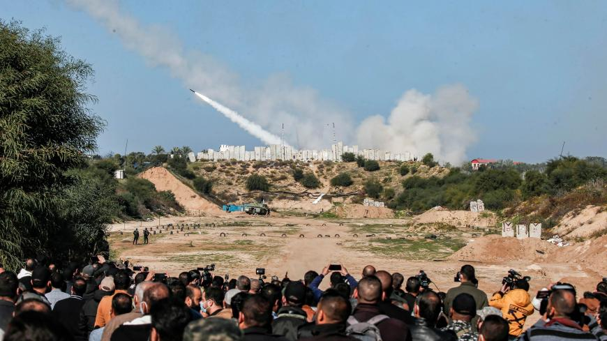 People watch as rockets are fired during a military drill by Palestinian Islamist movement Hamas and other Palestinian armed factions in Gaza City on December 29, 2020. (Photo by MAHMUD HAMS / AFP) (Photo by MAHMUD HAMS/AFP via Getty Images)