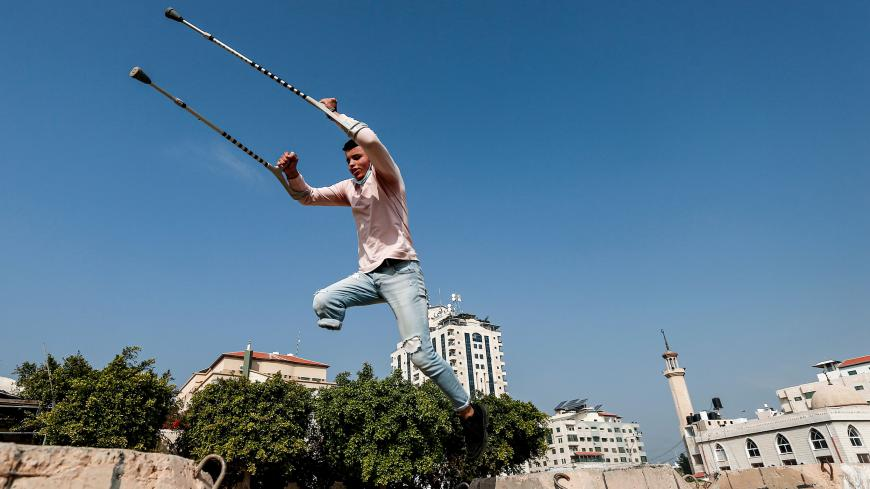 Mohamed Aliwa, a Palestinian youth whose leg was amputated near the knee in 2018 after he was hit by Israeli army fire during protests along the fortified border separating the Gaza Strip from Israel, shows off his parkour skills despite his disability and while on crutches in Gaza City on January 4, 2021. - Parkour, an extreme sport also known as free-running, originated in France in the 1990s. Young people in the Gaza Strip have been practising parkour for years; bounding from ruin to ruin in an enclave p