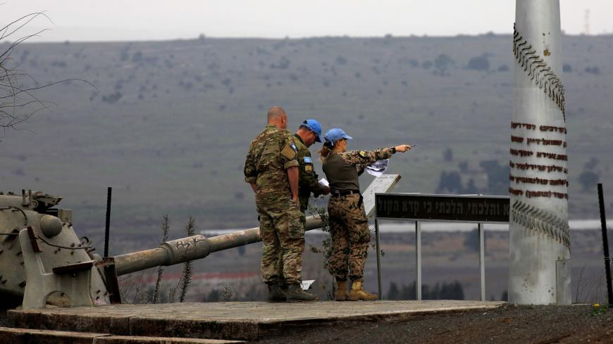 Memebers of the United Nations Disengagement Observer Force (UNDOF) stand near an old Israeli tank as they look toward the Syrian governorate of Quneitra from the Israeli-annexed Golan Heights, on February 4, 2021. (Photo by JALAA MAREY / AFP) (Photo by JALAA MAREY/AFP via Getty Images)