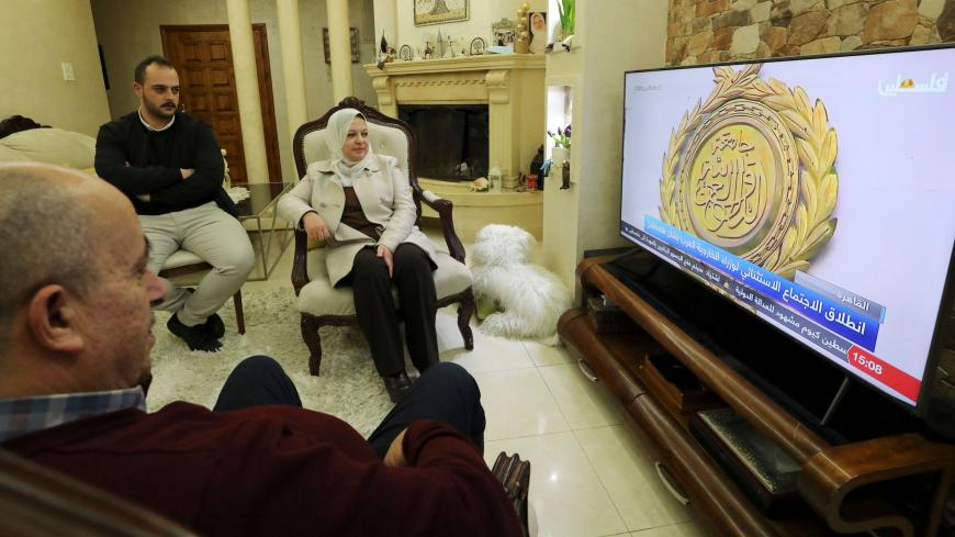 Sahar Qawasmeh (C), member of the Palestinian Legislative Council (PLC) representing the Fatah movement, watches the coverage of the Egypt-hosted Palestinian National Dialogue at her home in the the West Bank city of Hebron on February 8, 2021. (Photo by HAZEM BADER / AFP) (Photo by HAZEM BADER/AFP via Getty Images)