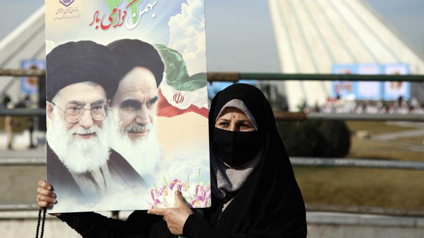 An Iranian woman holds a picture of Iranian supreme leader Ayatollah Ali Khamenei and former Iranian supreme leader Ayatollah Ruhollah Khomeini during a ceremony marking the 42nd anniversary of the 1979 Islamic Revolution, at the Azadi (Freedom) square in Tehran, on February 10 2021. (Photo by STR / AFP) (Photo by STR/AFP via Getty Images)