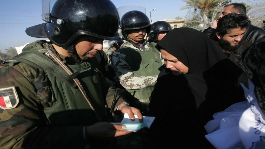 An Egyptian security officer checks the travel document of a Palestinian woman returning home through the one gate that remained open in the newly erected border fence between Egypt and the southern Gaza Strip town of Rafah, 03 February 2008. Egyptian and Hamas forces sealed off the border between Gaza and Egypt today after reportedly agreeing to control the frontier, blown open nearly two weeks ago amid an Israeli blockade. AFP PHOTO/MAHMUD HAMS (Photo credit should read MAHMUD HAMS/AFP via Getty Images)