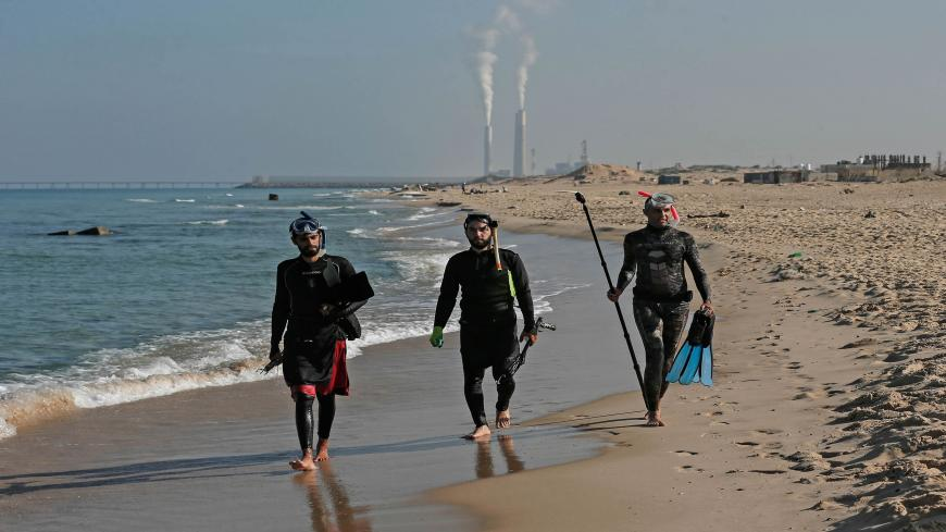 TOPSHOT - Palestinian spear-fishermen prepare to dive with an underwater photographer in the Mediterranean Sea, off the coast of Khan Yunis, in the southern Gaza Strip on October 15, 2020. (Photo by MAHMUD HAMS / AFP) (Photo by MAHMUD HAMS/AFP via Getty Images)