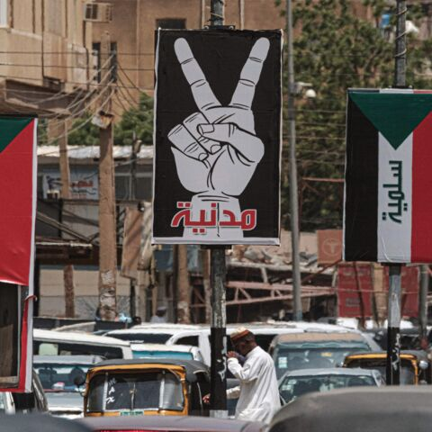 "This picture taken on June 15, 2019, shows placards showing the victory gesture with the Arabic word ""civilian"" and others of the Sudanese flag with the word ""peaceful"" along a street in the Sudanese capital, Khartoum."