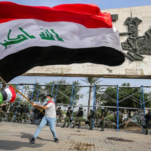 A demonstrator waves a large Iraqi national flag during an anti-government protest over corruption and poor services in Tahrir Square in the center of Iraq's capital, Baghdad, on Nov. 8, 2020.
