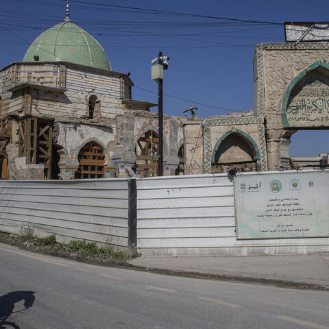 A man on a bicycle rides past Al-Nuri Mosque, which is under reconstruction after it was destroyed in the war against ISIS, on Feb. 28, 2021 in Mosul, Iraq.