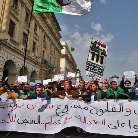 Algerians carry a large banner during an anti-government demonstration in the capital, Algiers, on April 2, 2021.