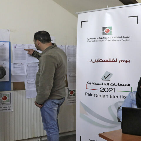 Employees of the Palestinian Central Elections Commission display electoral lists ahead of the upcoming general elections, at the commission's district offices, Hebron, West Bank, April 6, 2021.