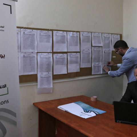 Employees of the Palestinian Central Elections Commission display electoral lists ahead of the upcoming general elections, at the commission's district offices in the city of Hebron in the Israeli-occupied West Bank, on April 6, 2021. Palestinian legislative elections are scheduled for May 22, with a presidential vote to follow on July 31.