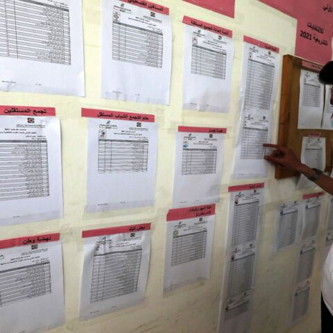 Staff of the Palestinian Central Elections Commission display electoral lists ahead of the upcoming general elections, at the commission's local offices in Ramallah in the occupied West Bank, on April 6, 2021.
