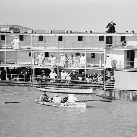 A Sudanese police officer is rowed to a passenger steamboat that has just arrived from Aswan at the Sudanese frontier town of Wadi Halfa on the River Nile, circa 1950.